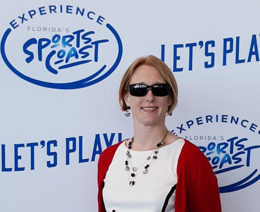 "Woman wearing sunglasses in front of ""let's play, Florida Sports Coast"" banner"